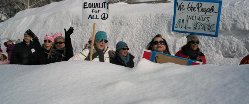 Women march behind shoulder high snow bank