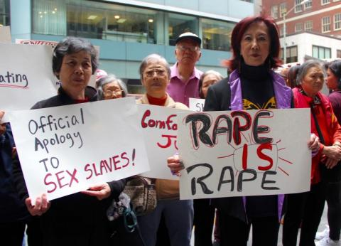 Protesters holding signs about abuse of women